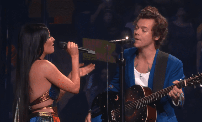 Harry Styles et al. singing on a stage