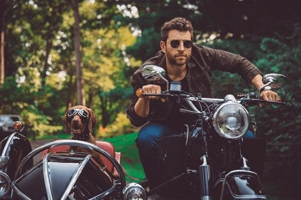 A man riding a motorcycle with a dog on the back
