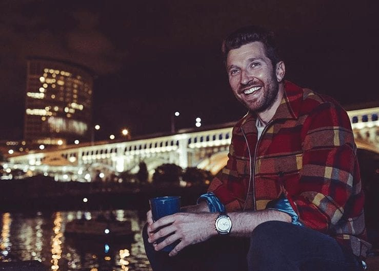 Brett Eldredge sitting on a ledge with a drink in his hand