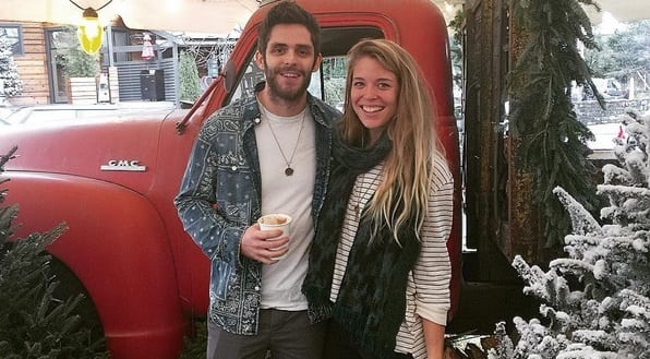 Thomas Rhett and woman posing for a picture next to a red car
