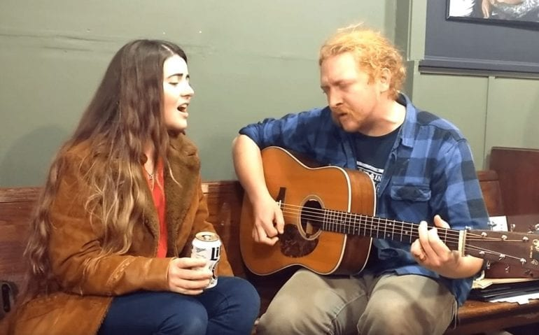 A man and woman playing guitars