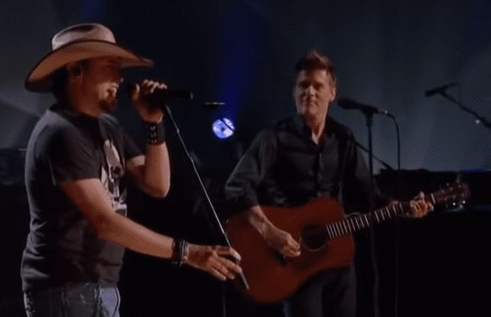 A man singing into a microphone next to a man playing guitar