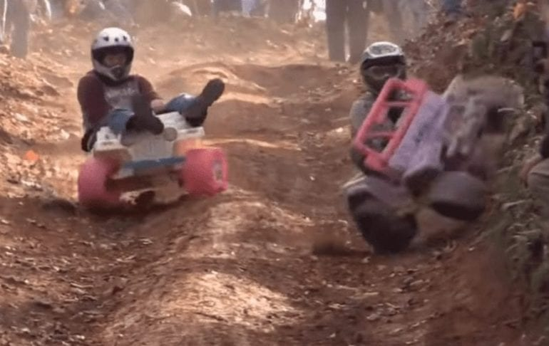 Two people riding toy vehicles on a dirt road