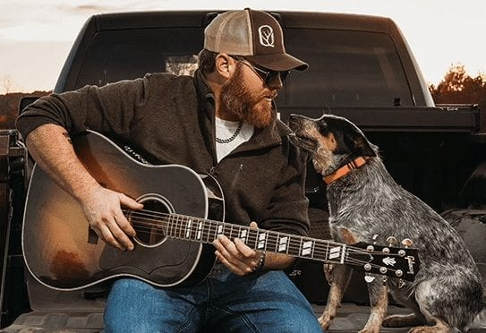 A man playing a guitar with a dog in a car