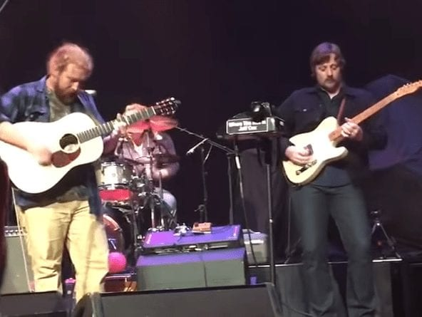 A group of men playing guitars on a stage