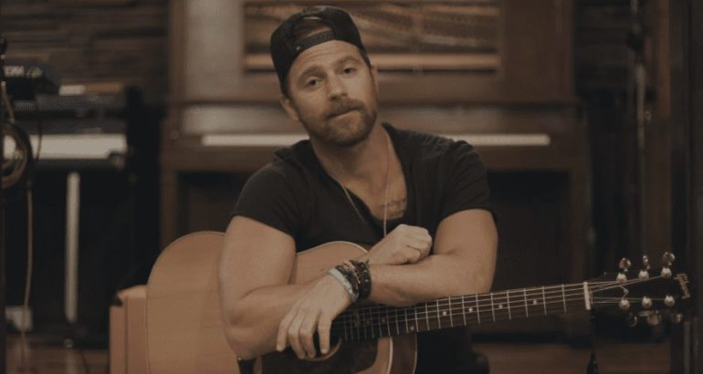 Kip Moore with a beard playing a guitar