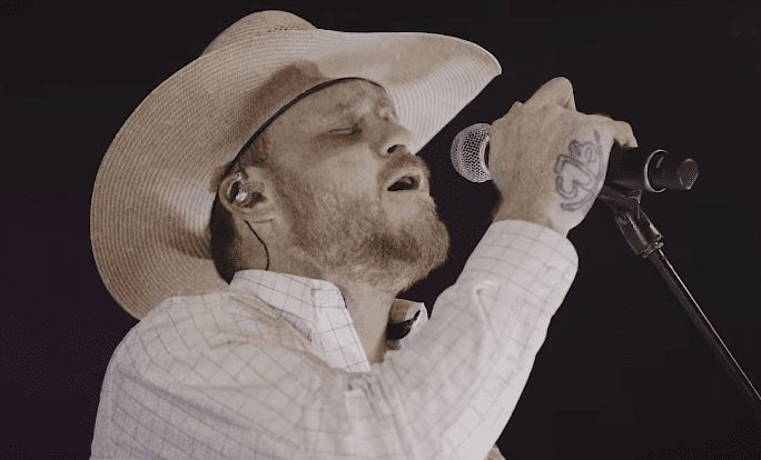 A man wearing a hat and holding a microphone
