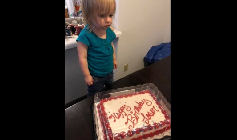 A child standing in front of a cake
