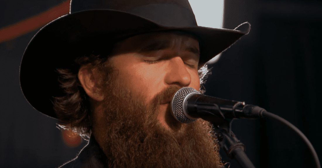 A man with a beard and a hat with a microphone in front of him