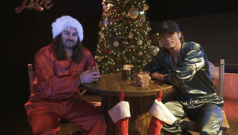 Two men sitting at a table with a christmas tree in the background