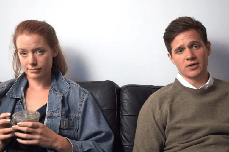 A man and a woman sitting on a couch and holding drinks