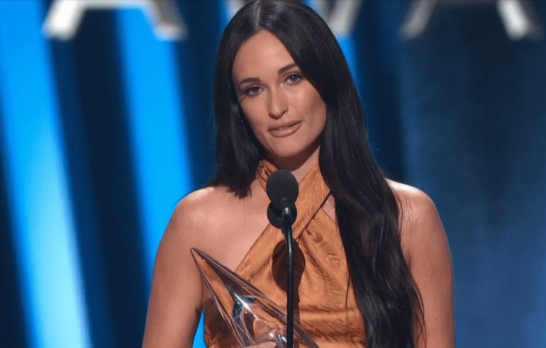 Kacey Musgraves wearing a brown robe and a microphone