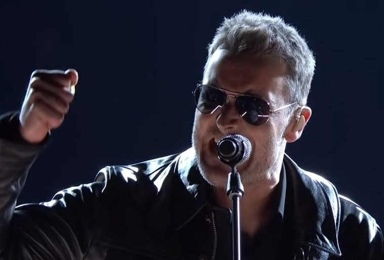 A man wearing sunglasses and holding a microphone