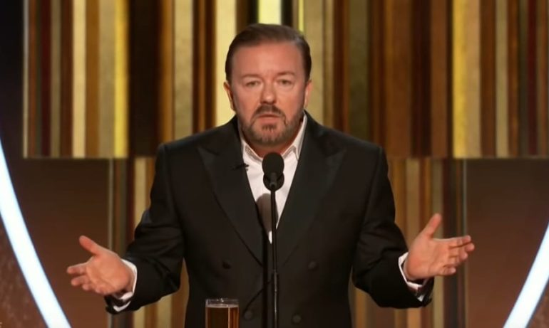 Ricky Gervais in a suit speaking into a microphone