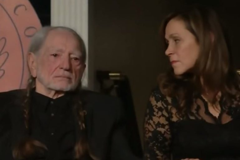 Willie Nelson and woman sitting next to each other