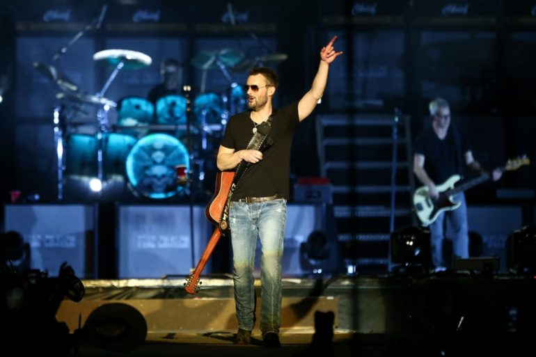 Eric Church holding a guitar and singing