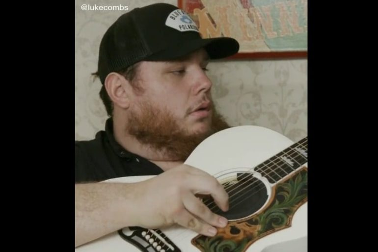 Luke Combs wearing a hat and holding a spoon