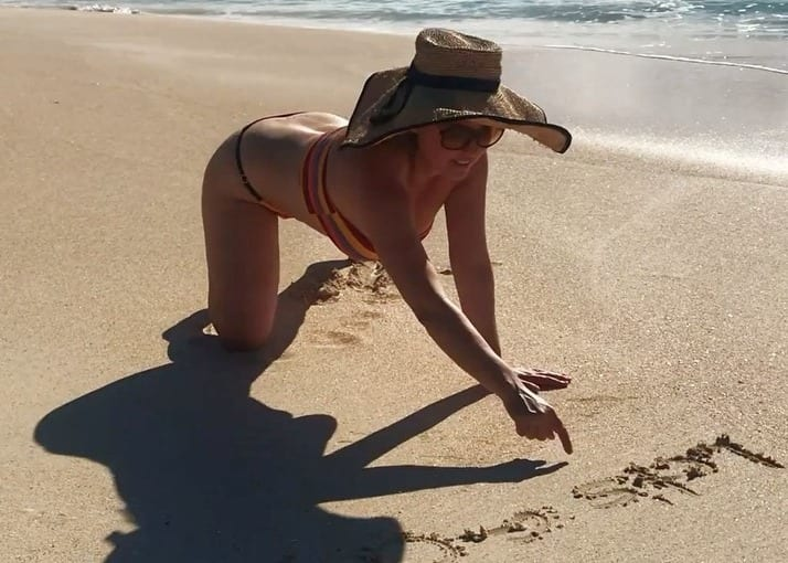 A woman in a hat and sunglasses on a beach