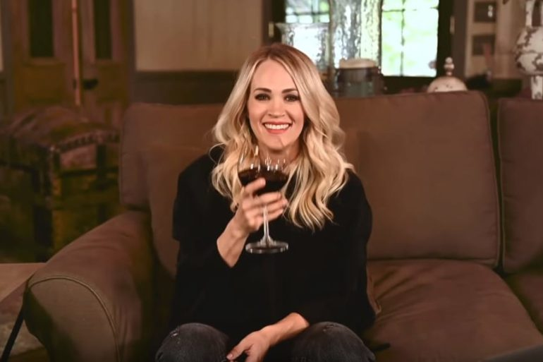 Carrie Underwood sitting on a couch holding a glass of wine