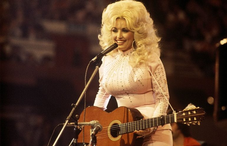 Dolly Parton wearing a white dress and playing a guitar