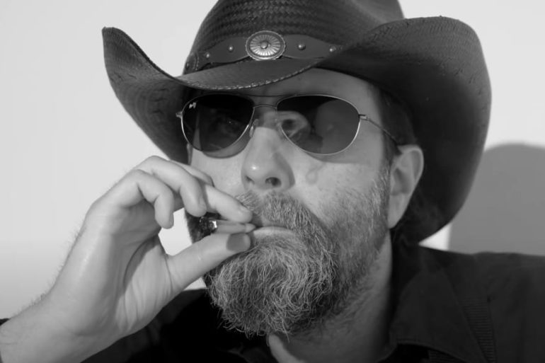 A man wearing a hat and smoking a cigarette
