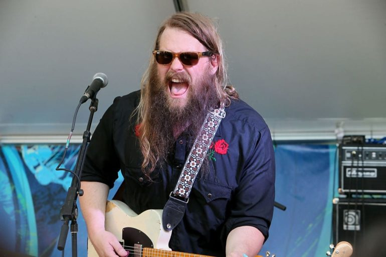 Chris Stapleton with long hair and a beard playing a guitar