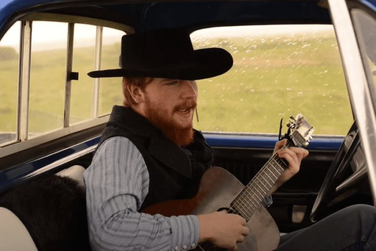 A man playing a guitar in a car