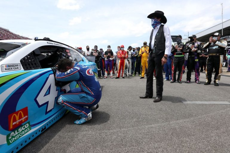 A person standing next to a race car with a person lying on the ground in front of him