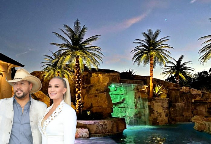 Jason Aldean and woman standing next to a pool with palm trees