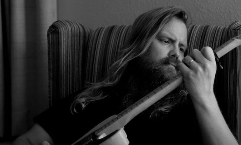 Chris Stapleton with long hair playing an instrument