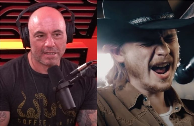 Joe Rogan with a mustache and a man with a microphone in front of him