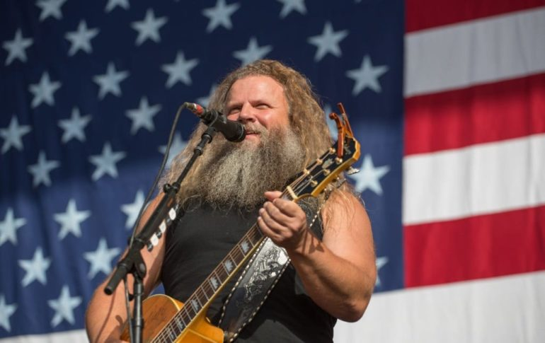 Jamey Johnson playing a guitar in front of a flag