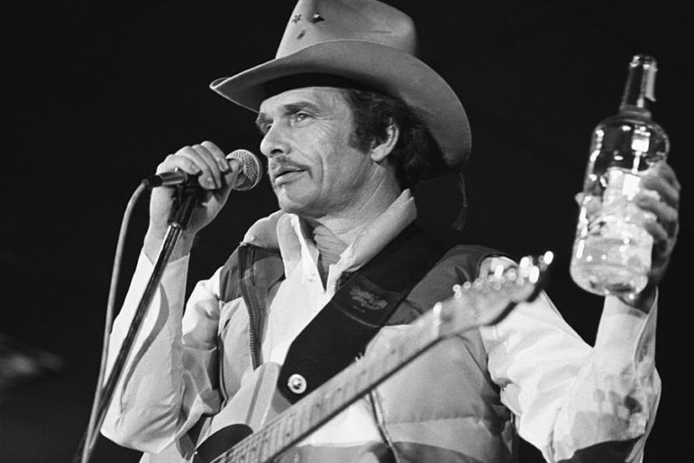 Merle Haggard holding a bottle of alcohol