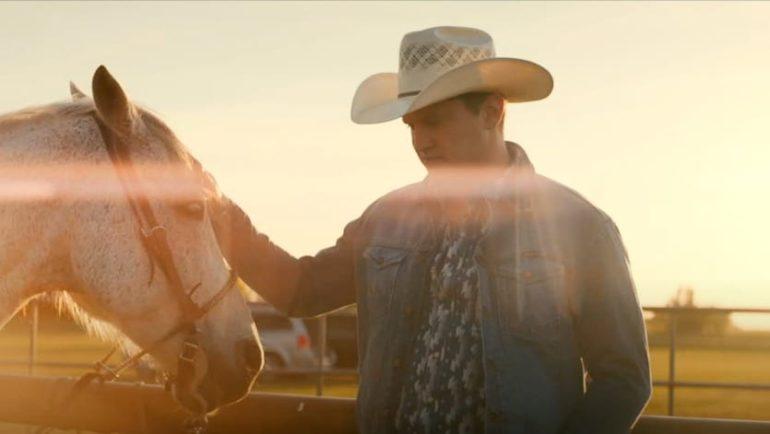 A man in cowboy hat sitting on a horse