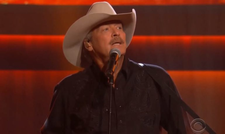 Alan Jackson wearing a cowboy hat and singing into a microphone