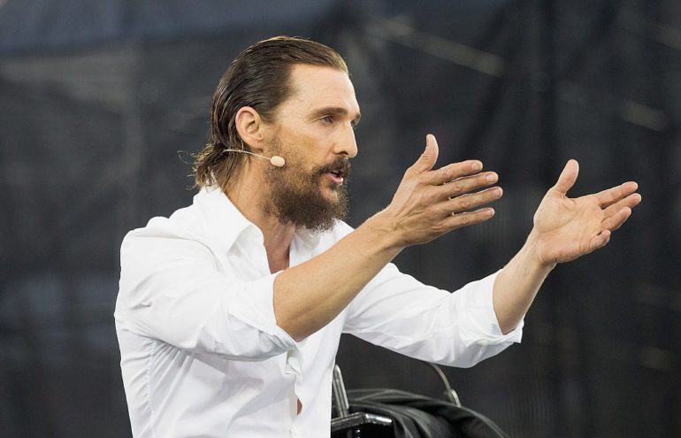 Matthew McConaughey with a beard and a microphone
