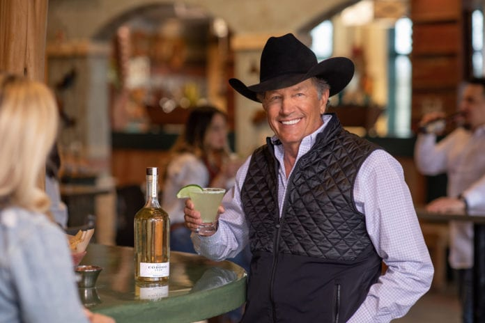 George Strait wearing a hat and smiling at the camera