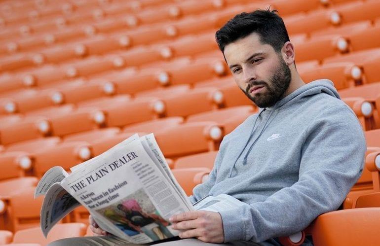 Baker Mayfield reading a newspaper