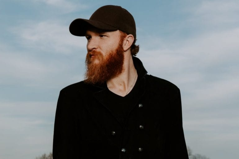 Eric Paslay with a beard and a hat