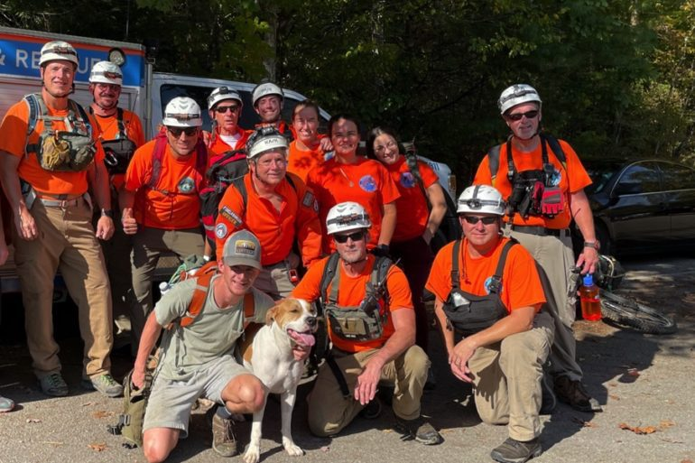 A group of people in orange vests and helmets with a dog