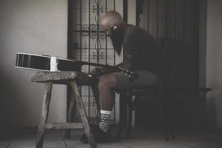 A man sitting on a bench playing a guitar