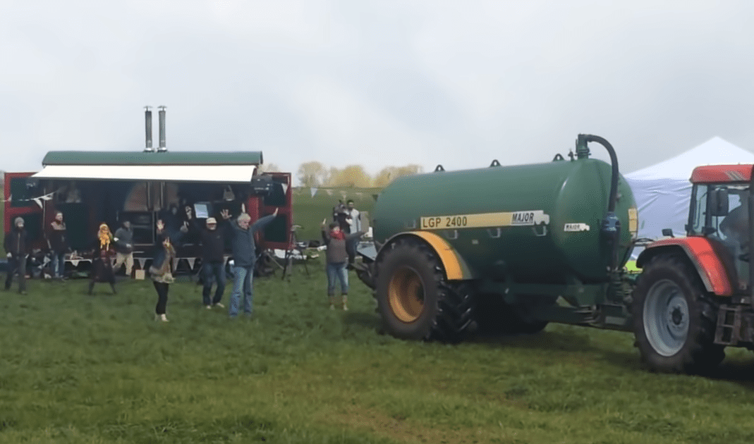A group of people standing around a green tractor