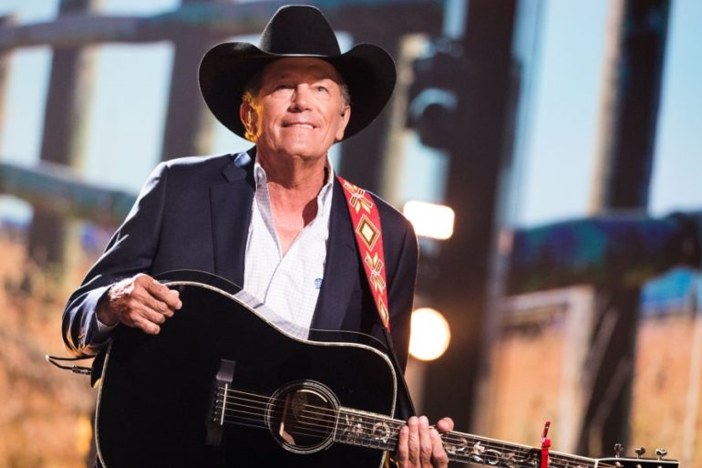 George Strait in a hat and a black jacket playing a guitar