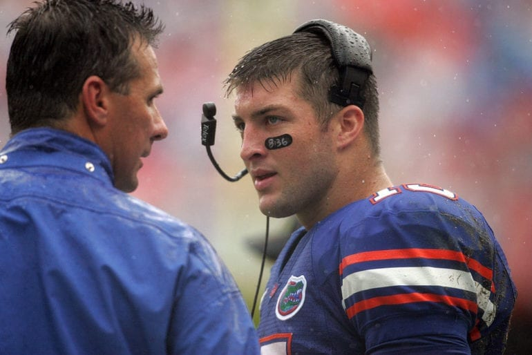 Tim Tebow in a blue shirt talking to a man in a blue uniform