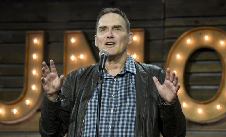 Norm MacDonald speaking into a microphone