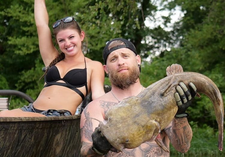 Brantley Gilbert and woman holding a large fish