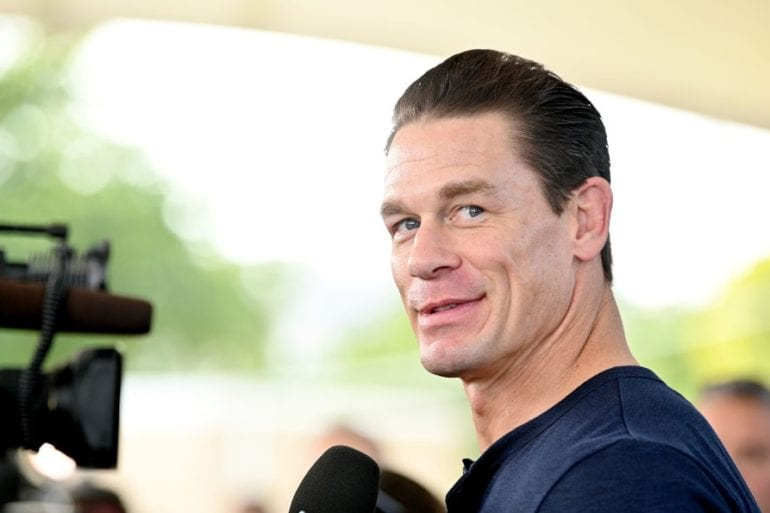 John Cena smiling in front of a microphone