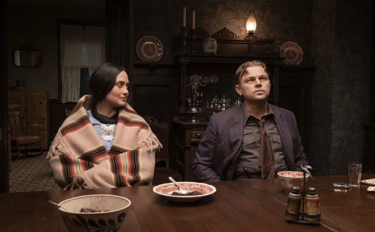 Leonardo DiCaprio, Lily Gladstone sitting at a table with food