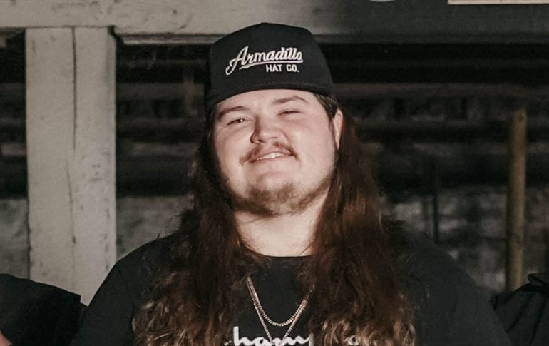 A man with long hair and a hat