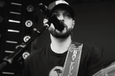A man with a beard and a hat holding a microphone